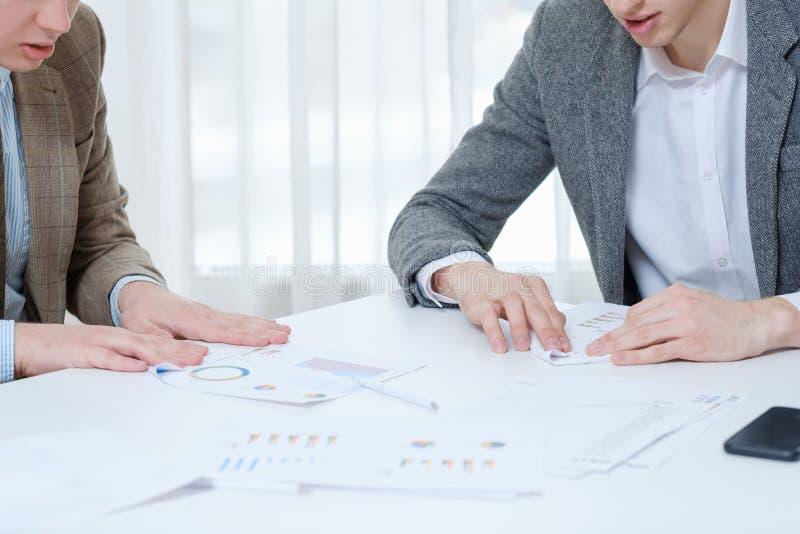 Geschäftsleute, welche die Papierflächen treffen Faulheit herstellen lizenzfreie stockfotos