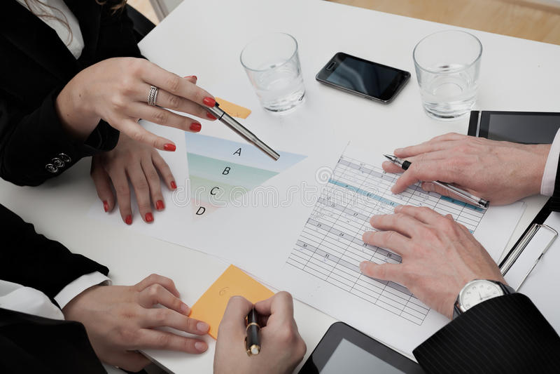 Geschäftsleute, welche die Tagesordnung analysieren stockfotos