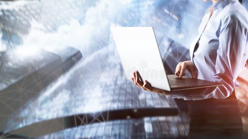 Geschäftsmädchen mit Laptop auf Stadthintergrund stockfoto
