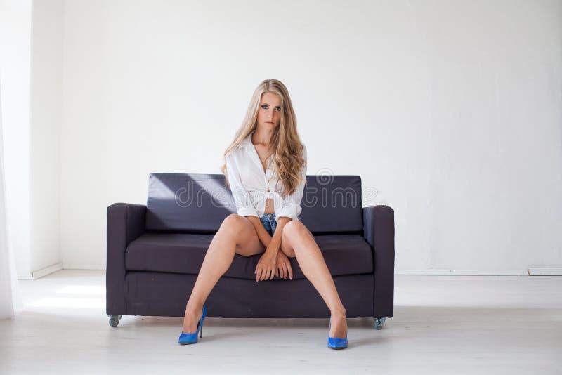 Geschäftsmädchenblondine sitzt auf einer schwarzen Couch im Büro lizenzfreie stockbilder