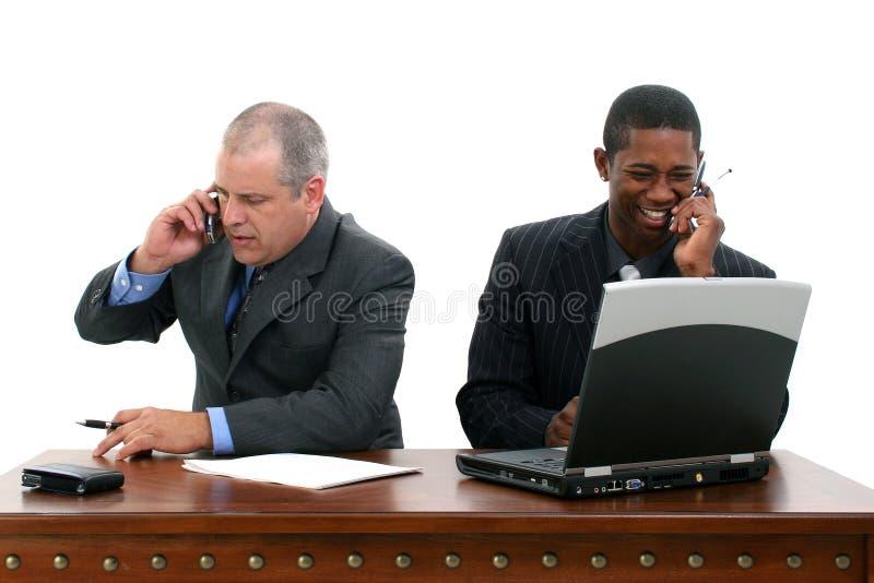 Geschäftsmänner auf Mobiltelefonen am Schreibtisch stockbild