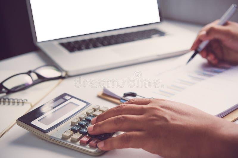 Geschäftsmänner benutzen einen Taschenrechner, um das Einkommen von Th zu berechnen lizenzfreies stockbild