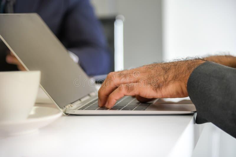 Geschäftsmänner benutzen Notizbücher, um Informationen zu verurteilen lizenzfreies stockfoto