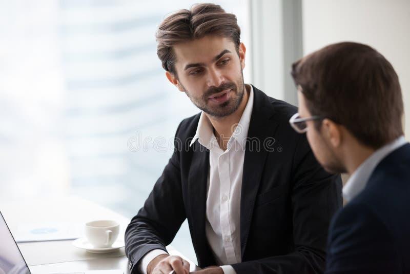 Geschäftsmänner in den Klagen besprechen Geschäftsideen im Büro stockfotos