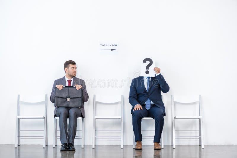 Geschäftsmänner in den Klagen, die auf Stühlen am weißen Warteraum sitzen lizenzfreies stockfoto