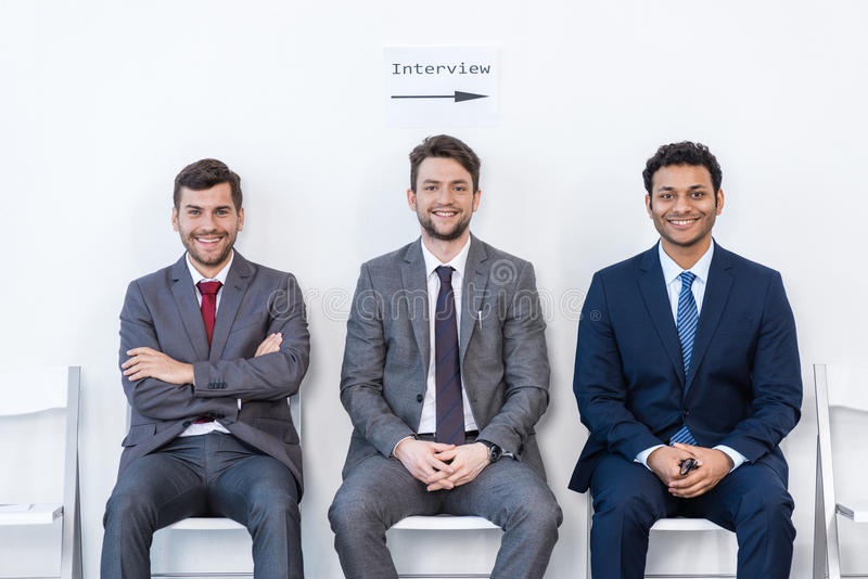 Geschäftsmänner in den Klagen, die auf Stühlen am weißen Warteraum sitzen stockfotografie