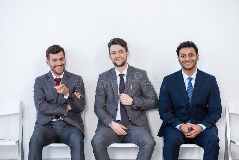 Geschäftsmänner in den Klagen, die auf Stühlen am weißen Warteraum sitzen lizenzfreie stockfotografie