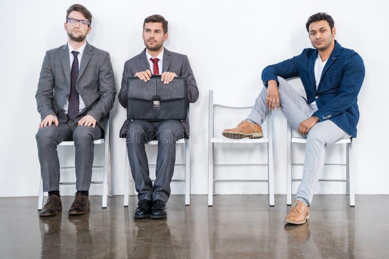 Geschäftsmänner in den Klagen sitzen auf Stühlen am weißen Warteraum stockfoto