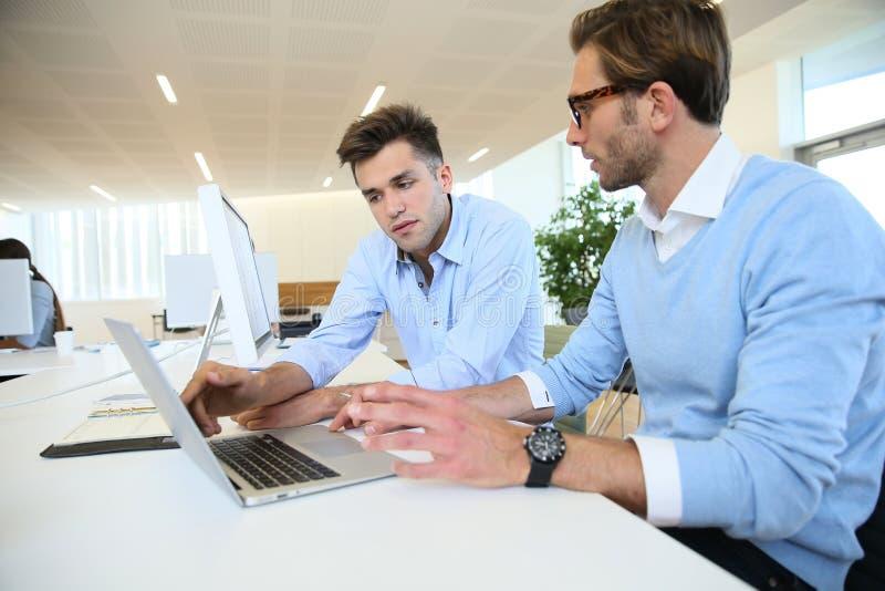 Geschäftsmänner an der Bürodiskussion stockfotografie