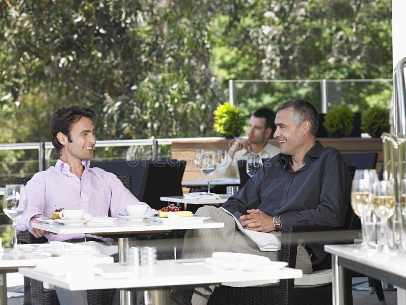 Geschäftsmänner, die Café am im Freien sich unterhalten stockbild