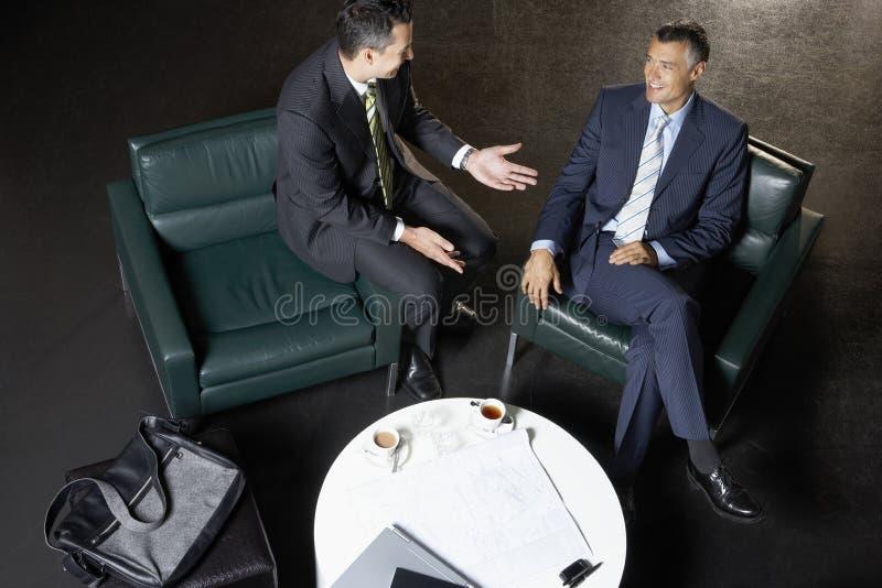 Geschäftsmänner, die am Couchtisch sich besprechen lizenzfreies stockbild