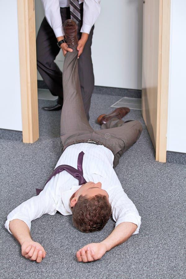 Geschäftsmänner, die das Bein des Kollegen im Büro ziehen lizenzfreie stockfotos