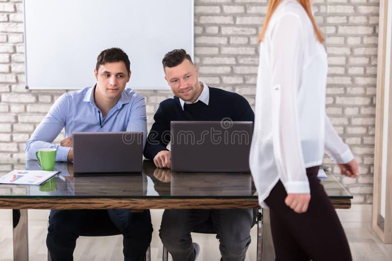 Geschäftsmänner, die Frau betrachten stockbilder