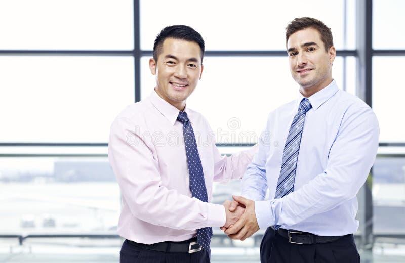 Geschäftsmänner, die Hände am Flughafen rütteln lizenzfreie stockbilder