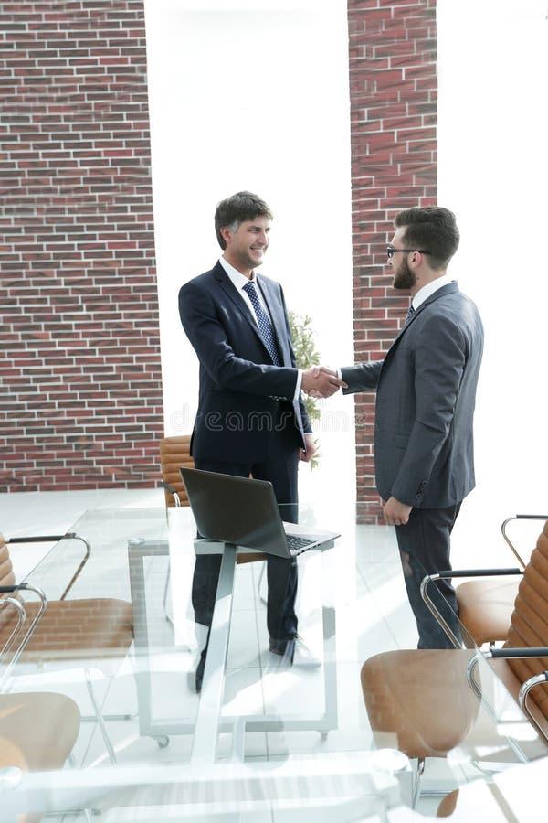 Geschäftsmänner, die Hände im Bürogebäude rütteln lizenzfreies stockfoto