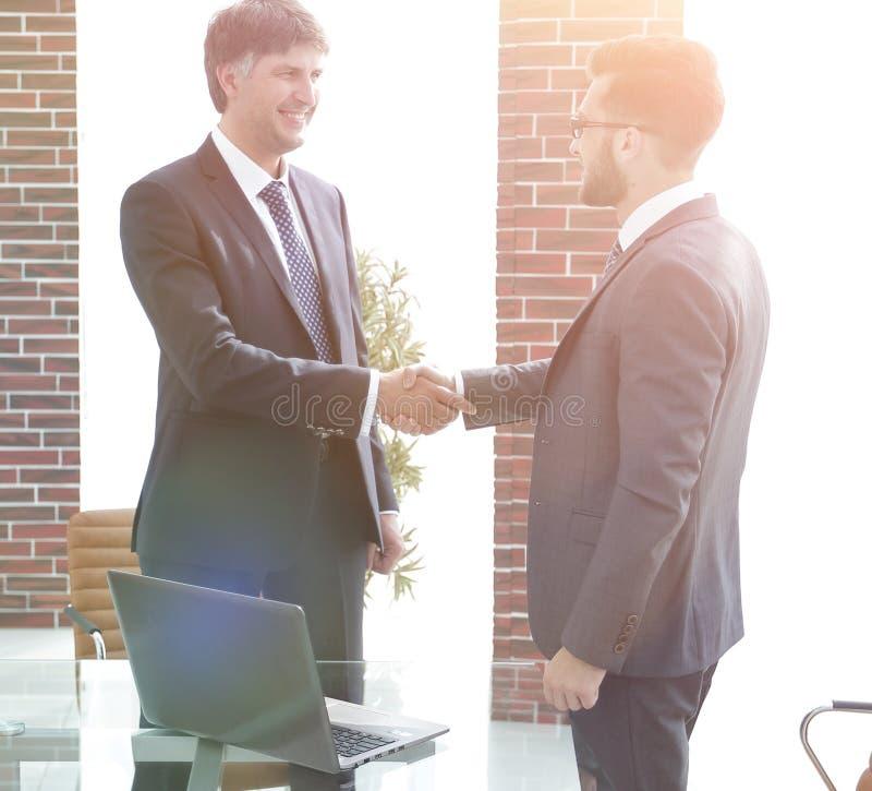 Geschäftsmänner, die Hände im Bürogebäude rütteln lizenzfreie stockfotos