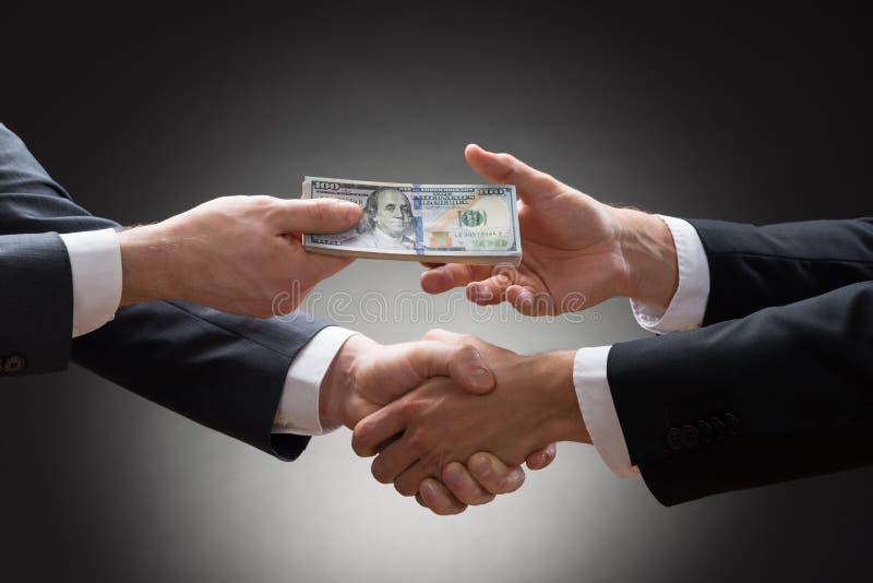 Geschäftsmänner, die Hände rütteln und Geld empfangen lizenzfreie stockfotos