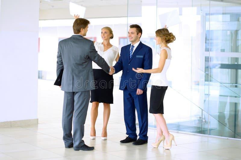 Geschäftsmänner, die Hände rütteln Zwei überzeugte Hände rüttelnde und bei der Stellung im Büro lächelnde Geschäftsmänner zusamme stockfotografie