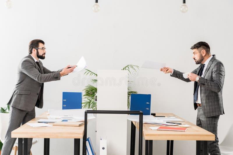 Geschäftsmänner, die im Büro streiten und Dokumente zeigen stockfotografie