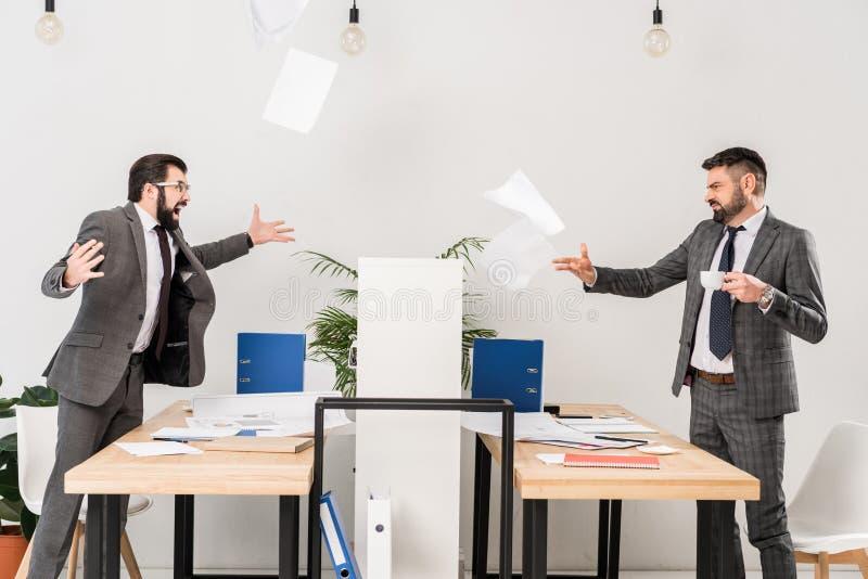 Geschäftsmänner, die im Büro streiten lizenzfreies stockfoto