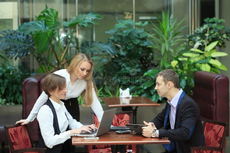 Geschäftsmänner, die im Café für einen Laptop sitzen stockbilder