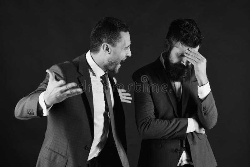 Geschäftsmänner, die laut auf schwarzem Hintergrund streiten stockfotos