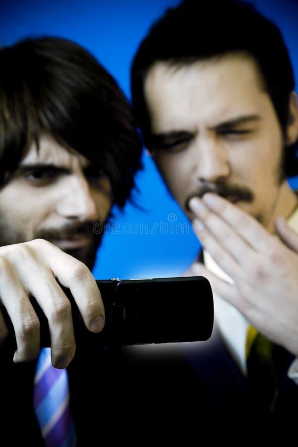 Geschäftsmänner, die Mobiltelefon studieren lizenzfreie stockfotografie