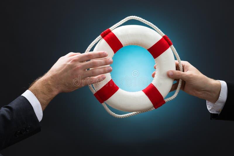 Geschäftsmänner, die Rettungsring über blauen Hintergrund führen lizenzfreies stockfoto