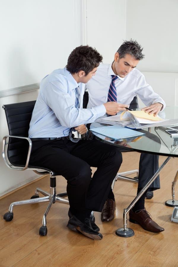 Geschäftsmänner, die Schreibarbeit im Büro besprechen stockfoto