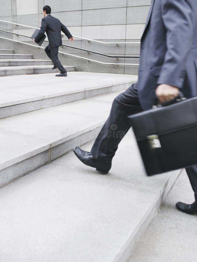 Geschäftsmänner, die sich draußen herauf Schritte beeilen lizenzfreie stockfotografie