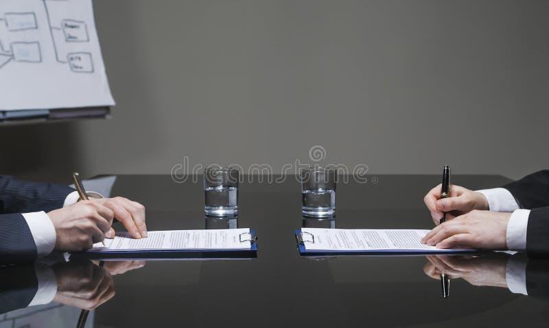 Geschäftsmänner, die Verträge unterzeichnen stockbild