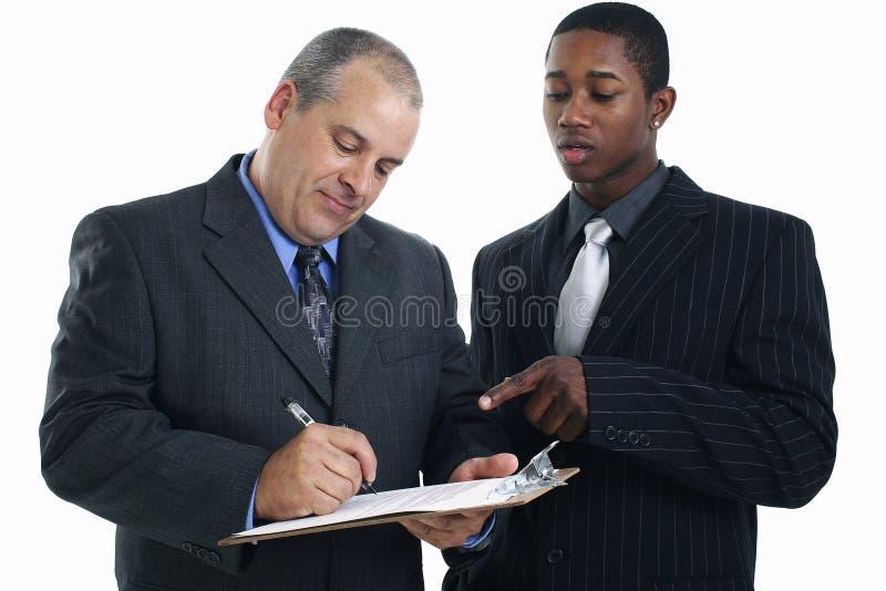 Geschäftsmänner, die Vertrag unterzeichnen stockbilder