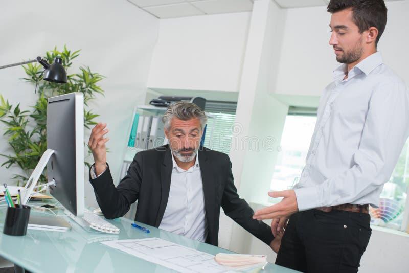 Geschäftsmänner, die wenn der interne Laptop debattieren, betrachtet wird lizenzfreie stockfotografie