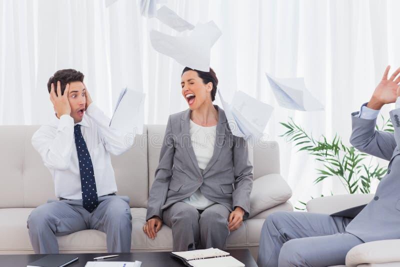 Geschäftsmänner entsetzt an schreienden und werfenden Papieren des Kollegen lizenzfreie stockfotografie