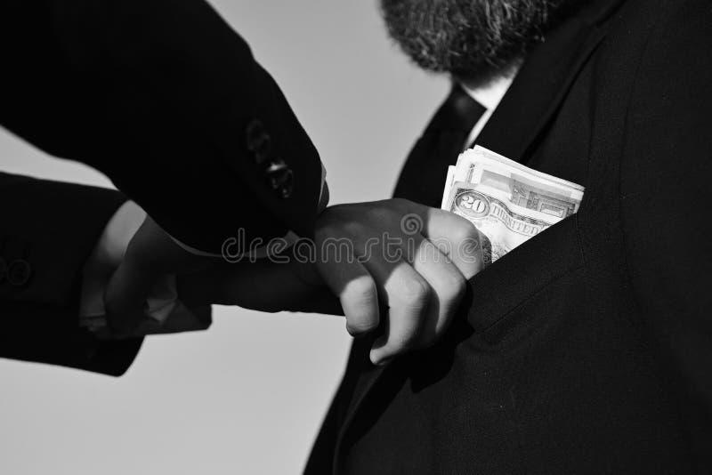 Geschäftsmänner schließen Handel ab Männliche Hand setzt Bargeld in Klagentasche stockbild
