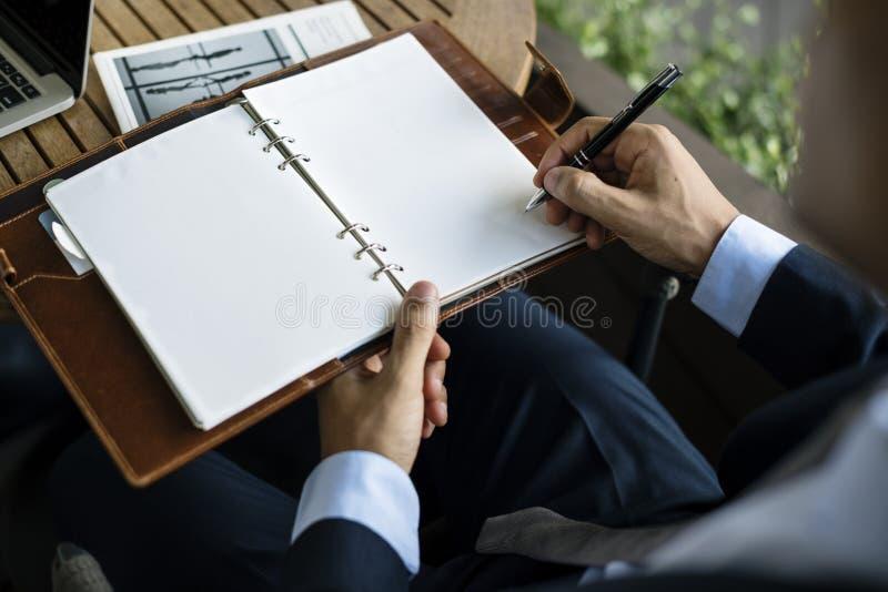 Geschäftsmänner schreiben Anmerkungs-Notizbuch-Plan stockfoto