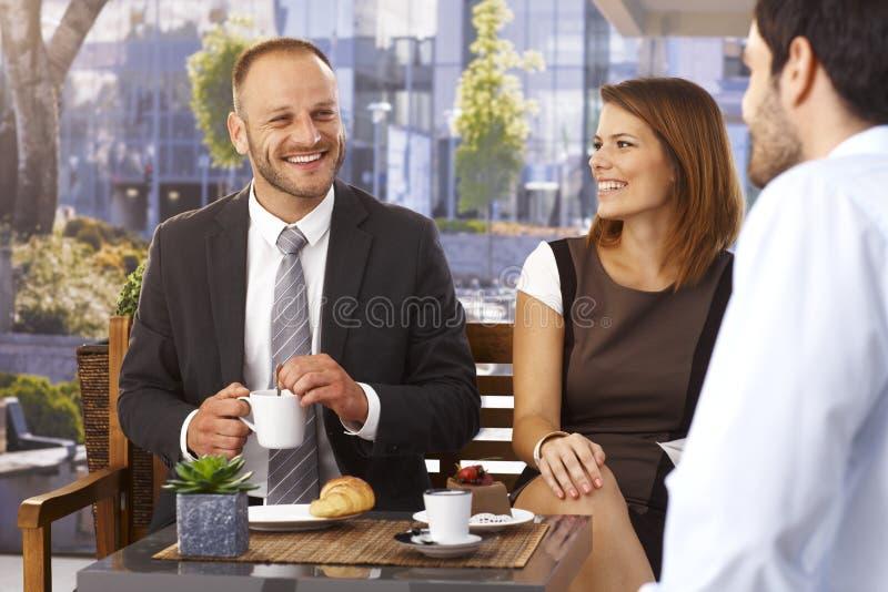 Geschäftsmänner und Geschäftsfrau, die am Café sich entspannen stockfotografie