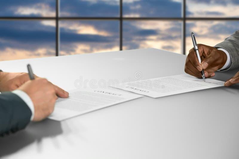 Geschäftsmänner unterzeichnen Verträge bei Sonnenuntergang lizenzfreies stockfoto