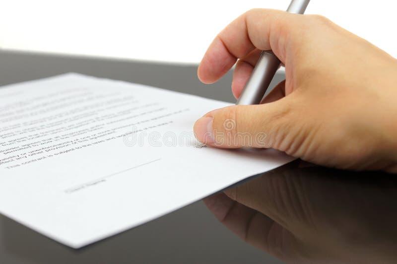 Geschäftsmann überprüft die Artikel der Vereinbarung, bevor er unterzeichnet stockfotos