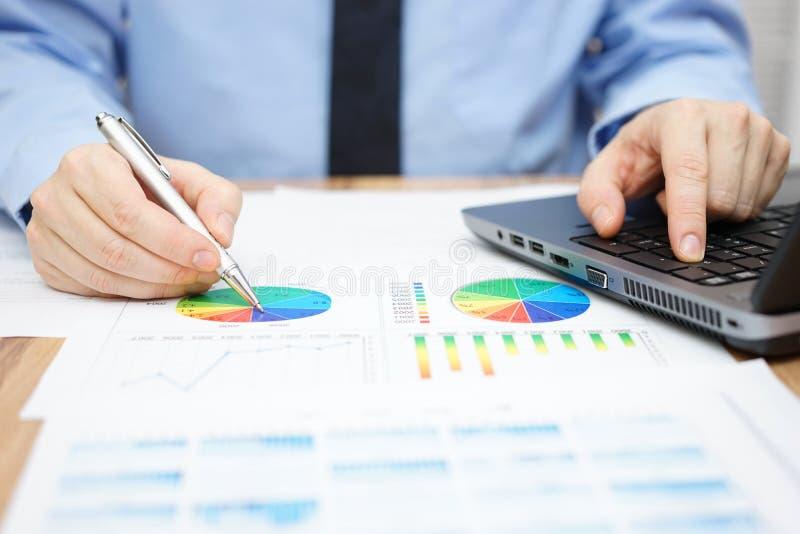 Geschäftsmann analysiert kommerzielle Daten und benutzt Laptop lizenzfreie stockbilder