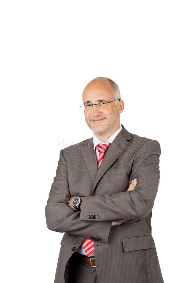 Geschäftsmann With Arms Crossed über weißem Hintergrund lizenzfreie stockfotografie
