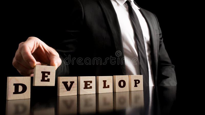 Geschäftsmann-Arranging Small Wooden-Stücke mit entwickeln Buchstaben stockfotografie