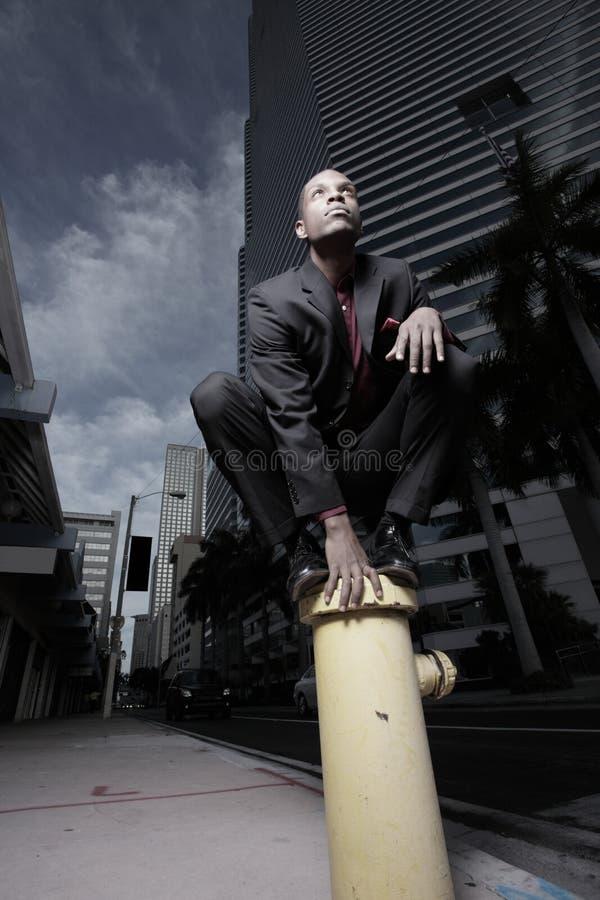 Geschäftsmann auf einem Feuerhydranten lizenzfreie stockfotografie