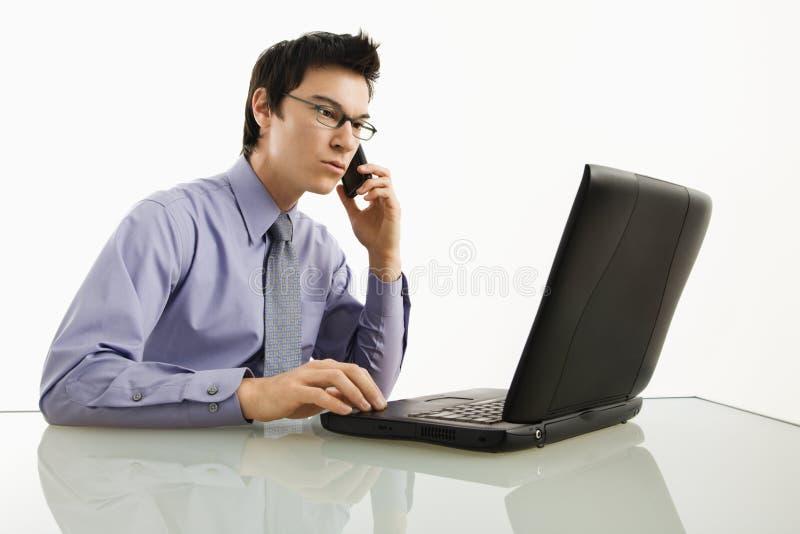 Geschäftsmann auf Laptop und Handy. stockbild
