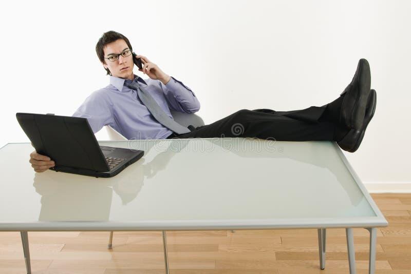 Geschäftsmann auf Laptop und Handy. lizenzfreie stockfotografie