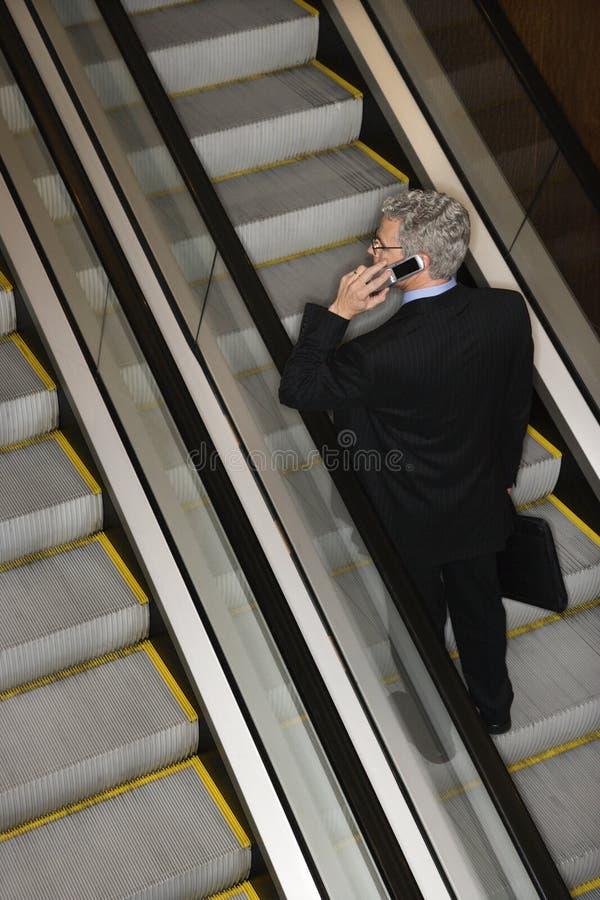 Geschäftsmann auf Rolltreppe mit Mobiltelefon stockfoto