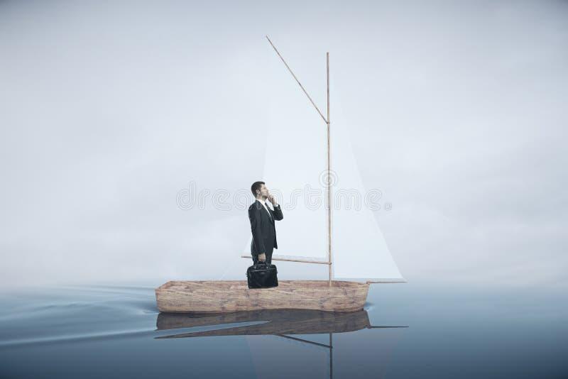 Geschäftsmann auf Segelboot stockfoto