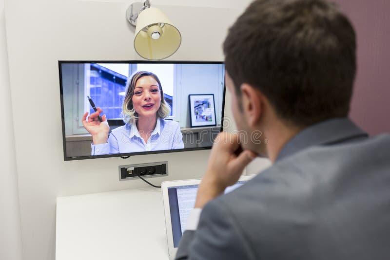 Geschäftsmann auf Videokonferenz mit ihrem Kollegen im Bürojob lizenzfreie stockfotografie