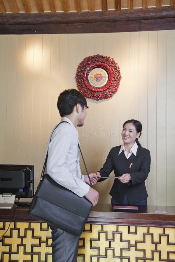 Geschäftsmann am Aufnahme-Schreibtisch des Hotels stockfotos