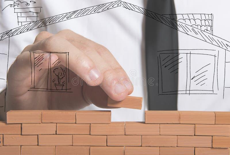 Geschäftsmann baut ein neues Haus auf lizenzfreies stockbild